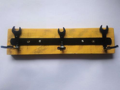 Black spanner coat rack on yellow backing