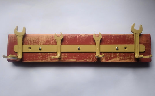 Yellow spanner coat rack on red backing
