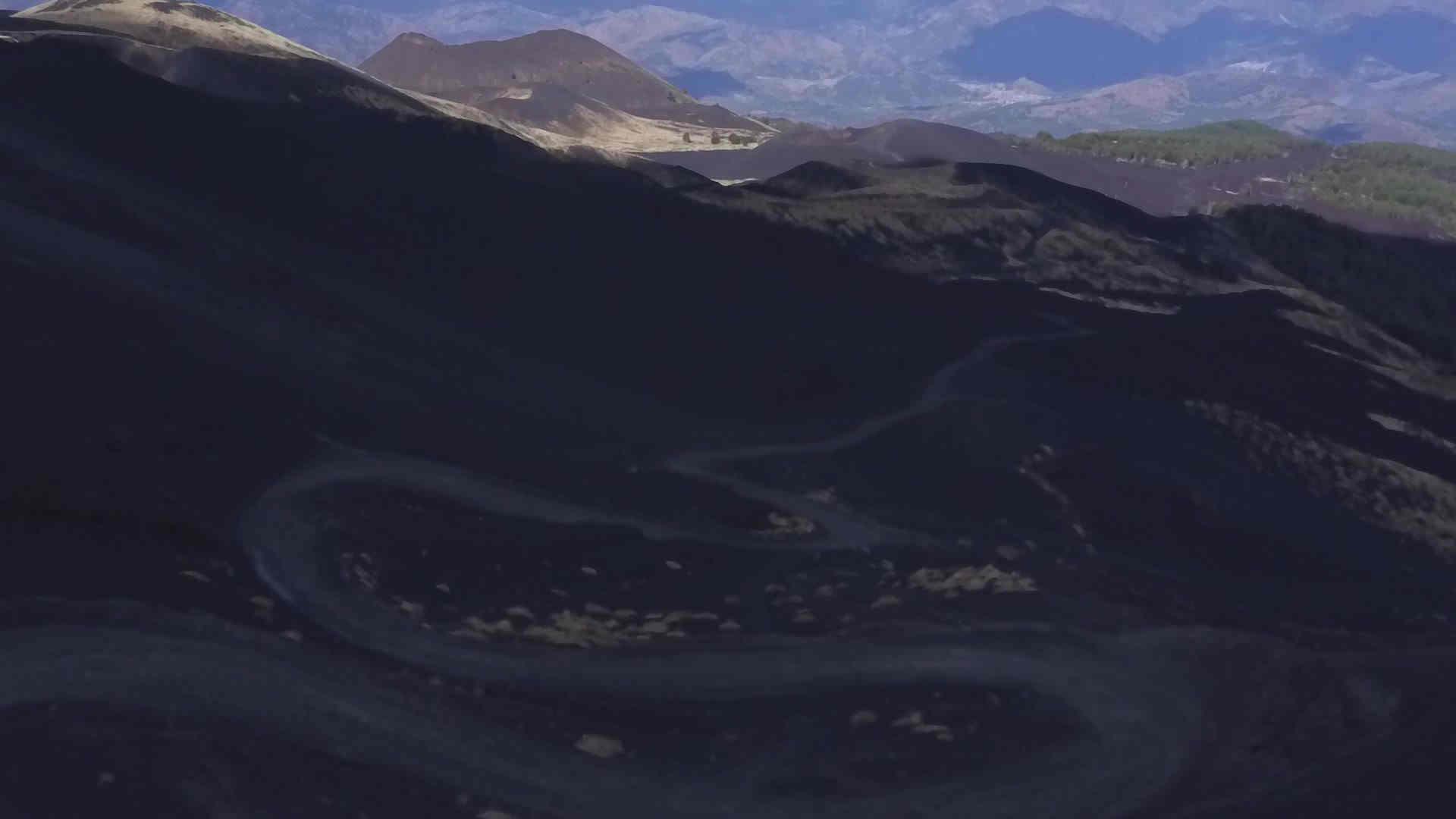 Ripresa aerea di una ragazza che fa un'escursione sull'Etna,