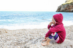 Pensive girl relaxing on a pebbly beach,