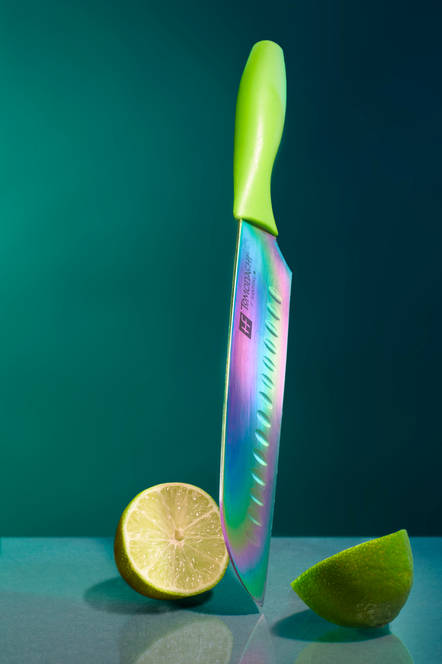 Studio commercial photography of a rainbow Tomadachi knife slicing a lime