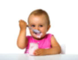 baby eating yogurt with a spoon