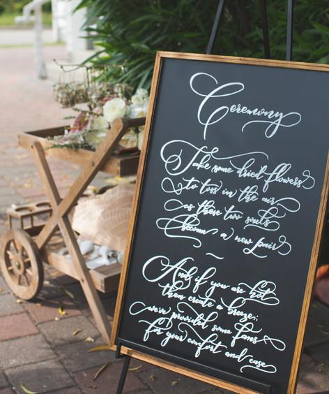 Outdoor Beach Wedding Ceremony Chalkboard Sign Fans Dried Flower Confetti.jpg