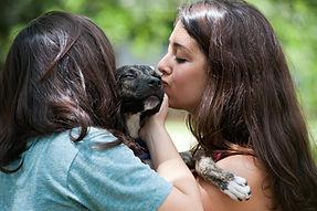girls kissing dog