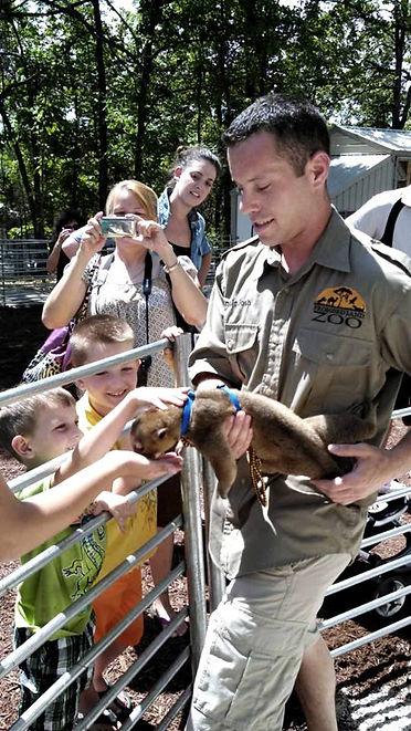 feeding a baby monkey, kids in a petting zoo, family vacation