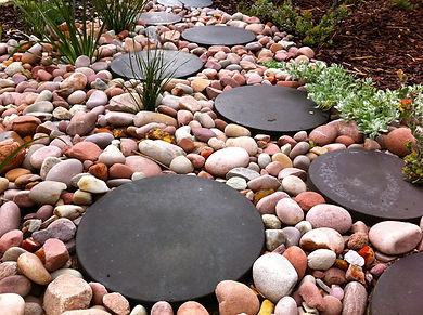 Round riverstone in garden with black concrete stepping stone edged by plants