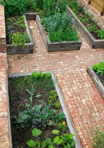 Railway sleepers used for raised vegtable garden with recycled brick pathways