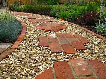 Cleaned recycled bricks used in pathway as stepping stone with brick edge filled with white pebble