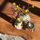 Wooden coffee table in the Bergner Alm Apartment with wild alpine flowers