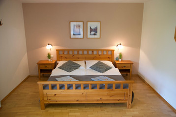 Bedroom one in the Bergner Alm apartment with a large double bed, separate single bed, and cosy features