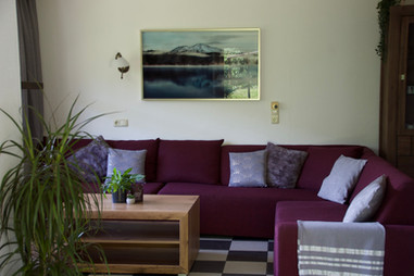 Large living room in the Bergner Alm apartment, with a large 9 person couch and flat screen TV