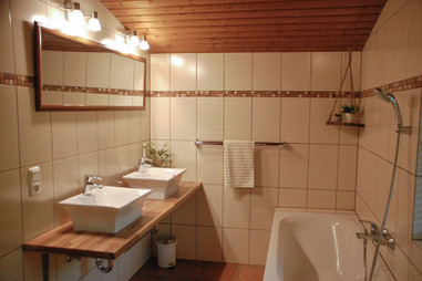 Bathroom in the Edelweiss Spitze apartment with large bath, separate shower, double sinks, towel warmer & separate WC