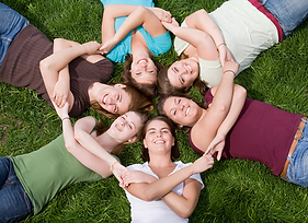 six girls holding hands while lying down in a circle on the grass