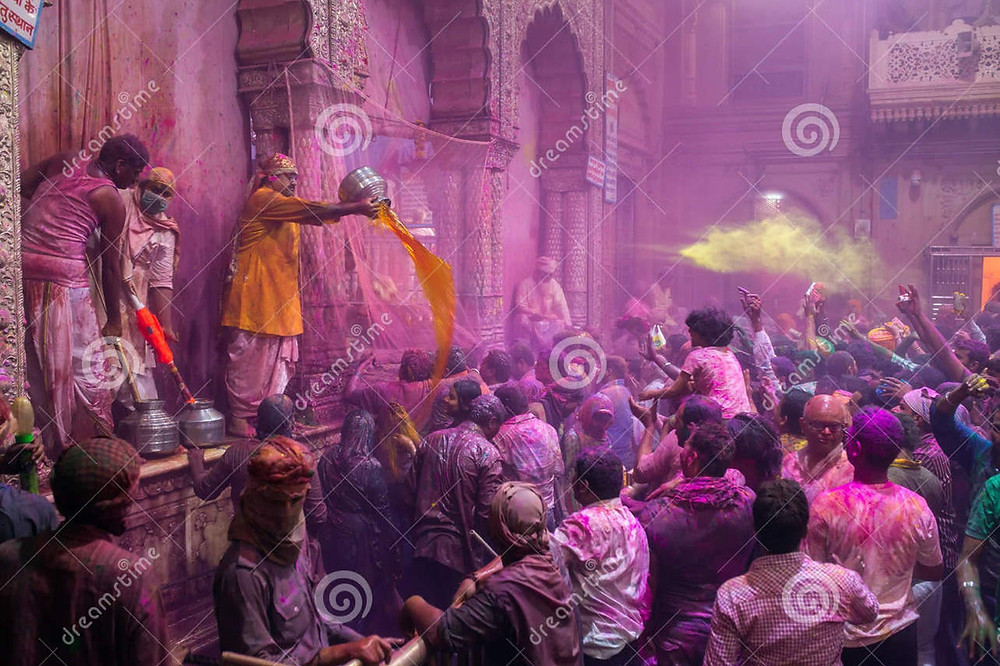 A group of Indian people playing with wet Holi colors in the street.