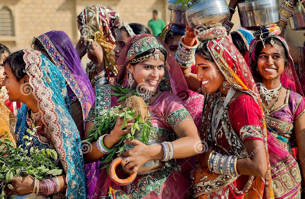 This is a picture of nine young Indian women who are all wearing Sarees of different colors. The women are smiling, and they're also wearing other traditional accessories, such as bangles.
