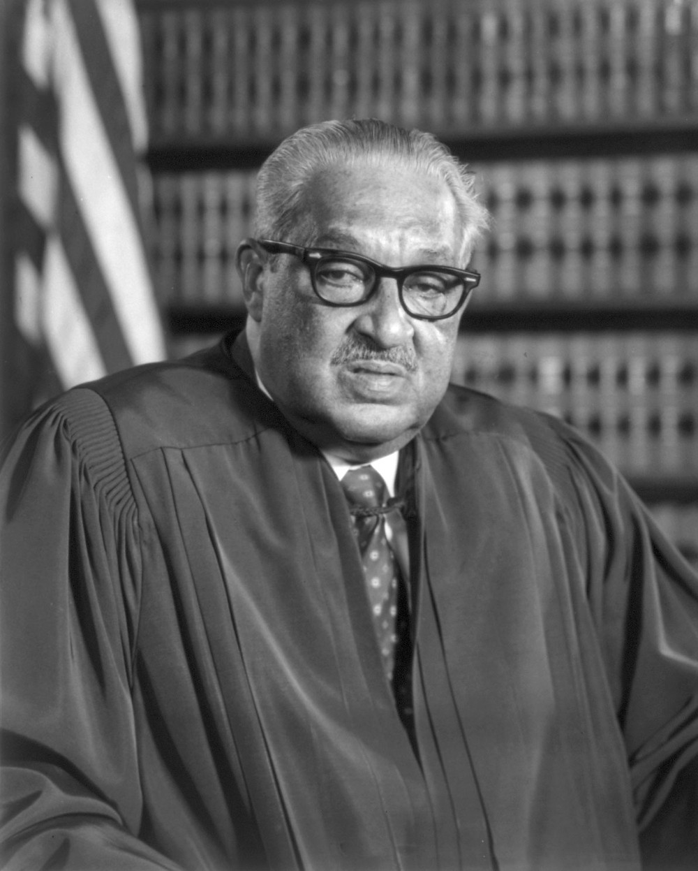 This is a black and white portrait of Thurgood Marshall, a Black man with short, gray hair. He's wearing judge's robes and glasses, and he's standing in front of a bookcase and an American flag.