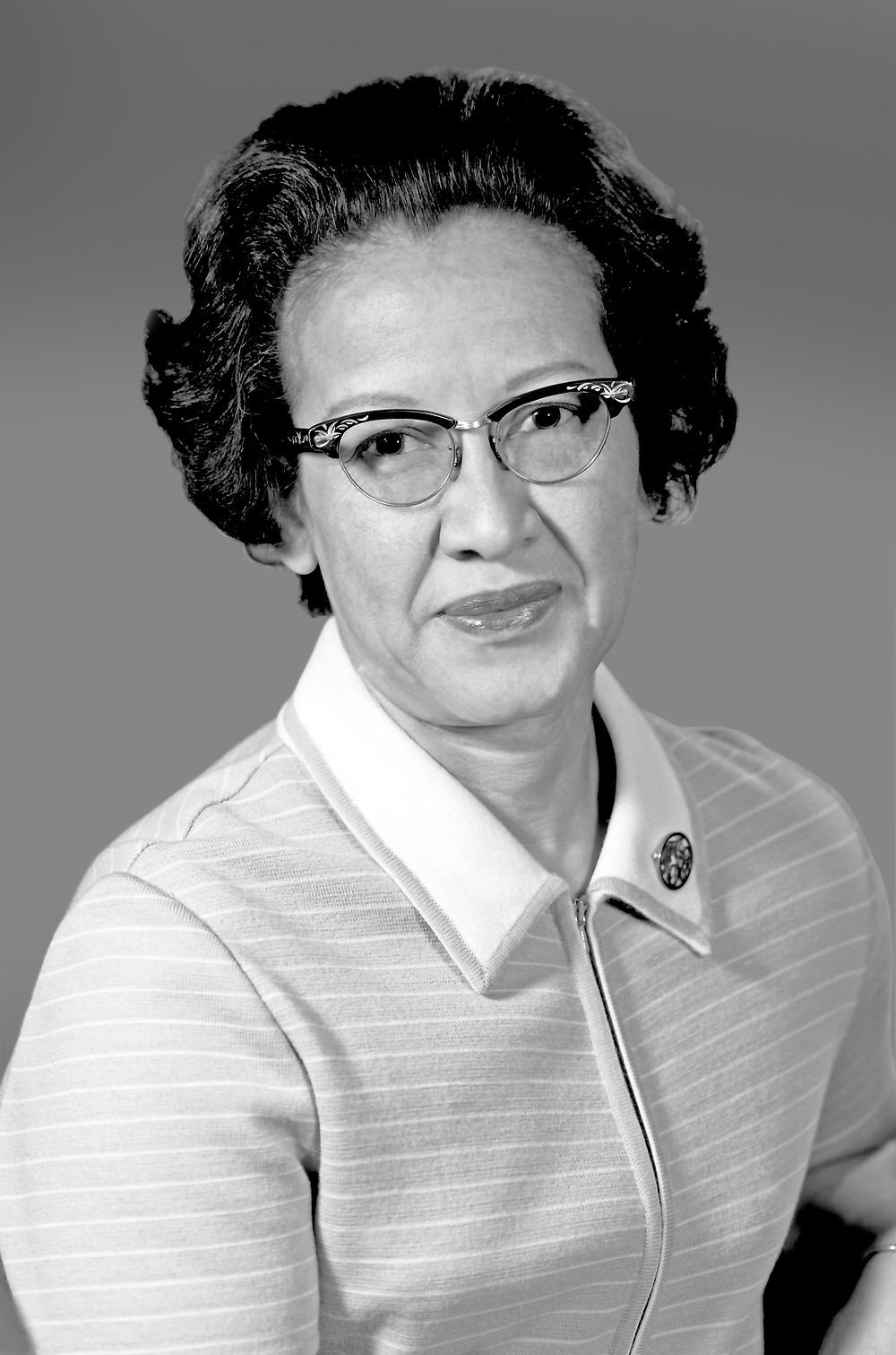 This is a black-and-white portrait of Katherine Johnson, a Black woman with short, black hair. She's wearing glasses and a light colored, striped, collar shirt.