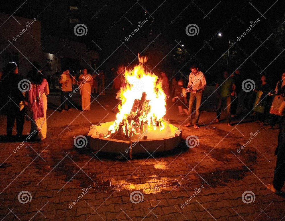 A group of Indian men and women gathered around a Holi bonfire.