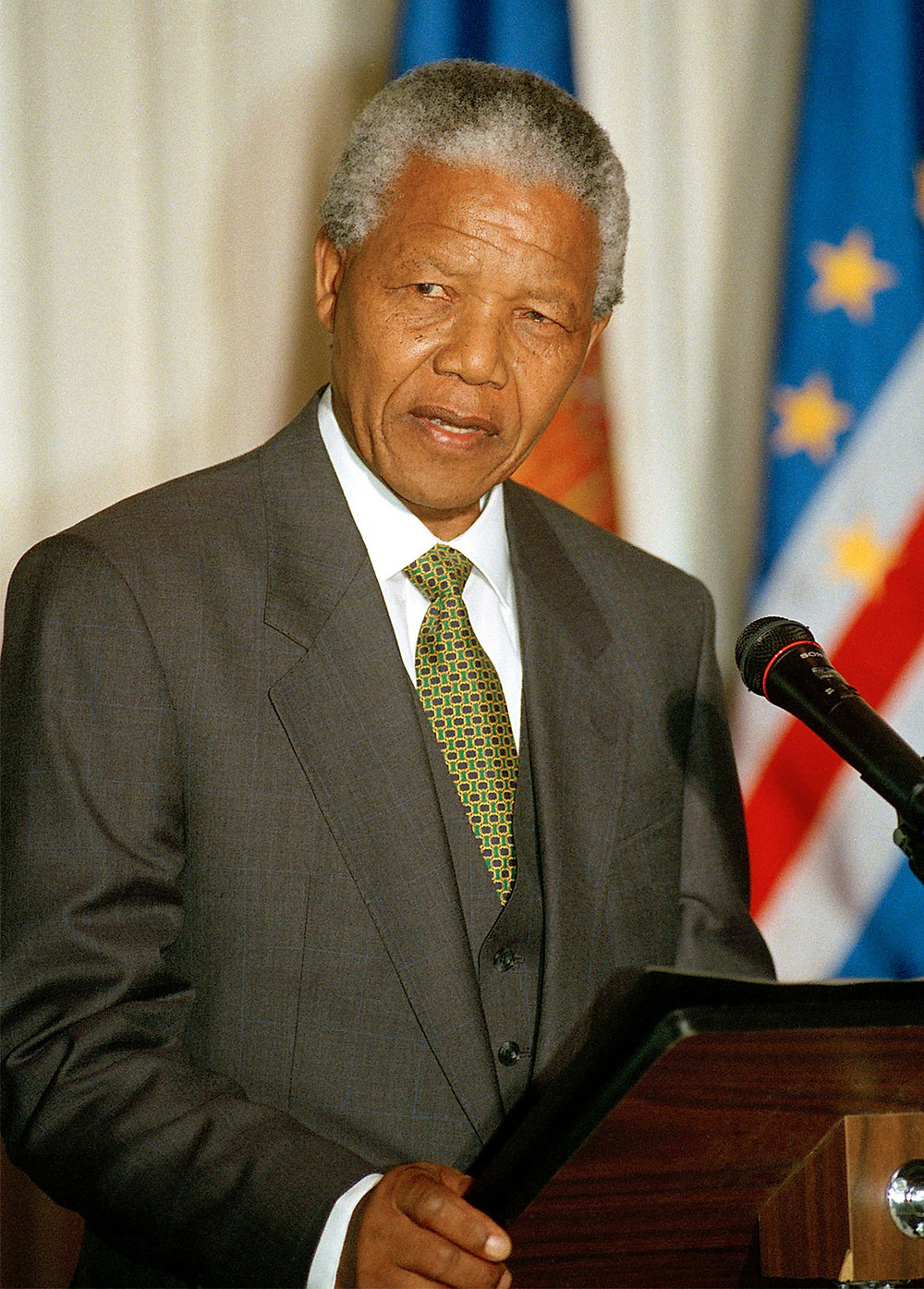 This is a portrait of Nelson Mandela, a Black man. He has salt and pepper hair, and he's wearing a gray suit, a white dress shirt, and a green tie. He's standing behind a podium, and there are a couple of large flags behind him.