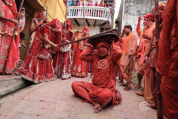 This is a picture of an Indian man sitting in the street with a shield over his head. A woman is standing off to the side and hitting the shield with a stick. The man is surrounded by other people, all wearing various shades of red.