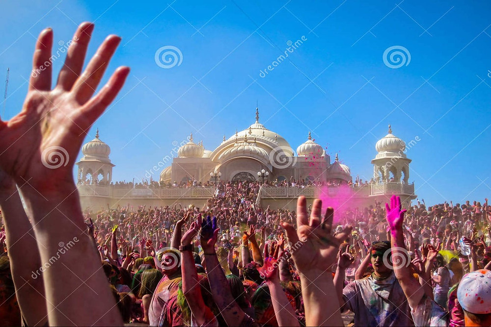 This is a picture of thousands of people celebrating Holi at the Krishna temple in Salt Lake City, Utah.