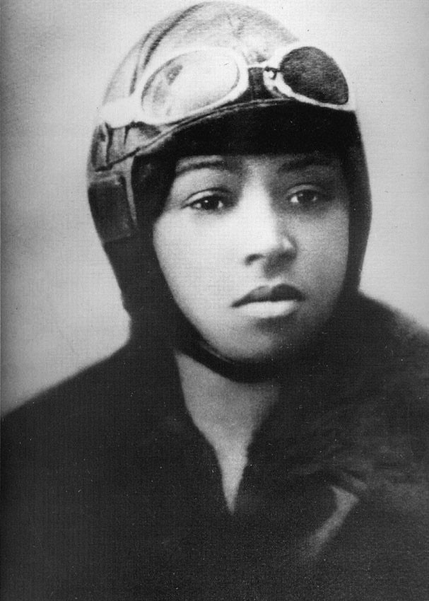 This is a black-and-white portrait of Bessie Coleman, a Black woman. She's wearing an aviator hat, goggles, and a bomber jacket.