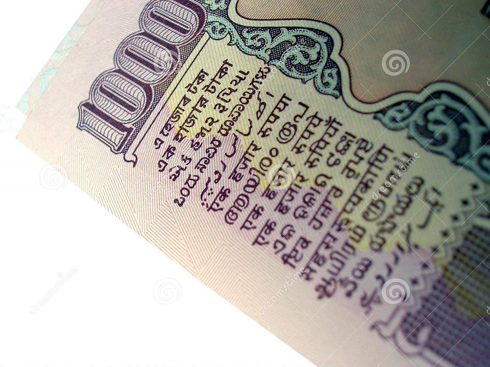 This is a picture of a 1000 Rupee note. On the side of the note are 15 lines, each written in one of the Indian languages.