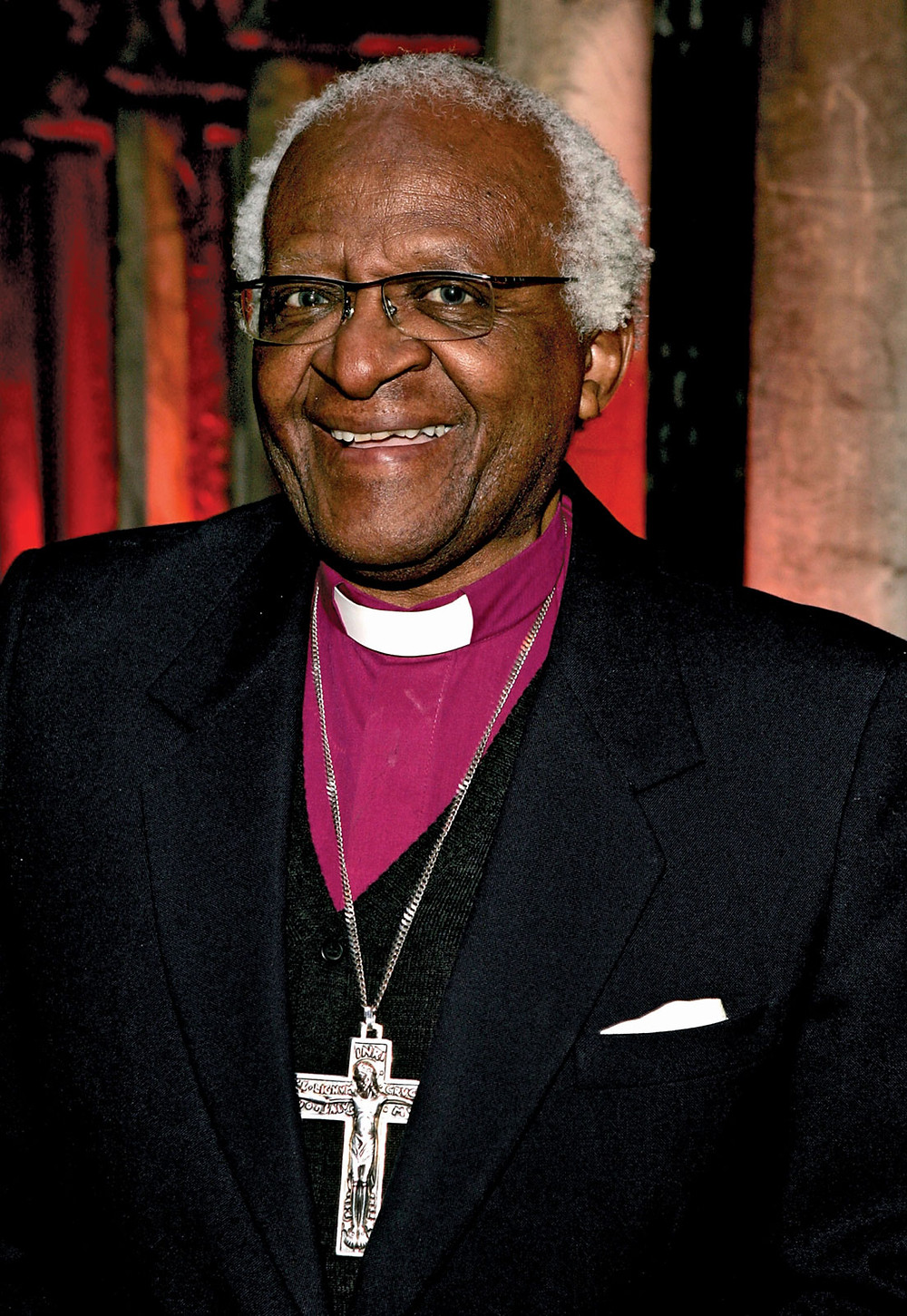 This is a portrait of Desmond Tutu, a Black man. He's pictured wearing a magenta shirt with a white Clerical collar, a black suit jacket, and a large silver crucifix around his neck. He also wears glasses and has short, silver hair.