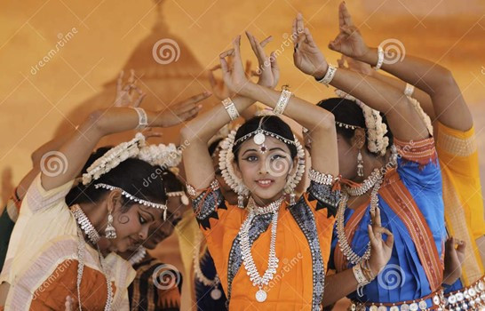 This is a picture of four young Indian women who are dressed in traditional clothes. They're wearing traditional clothes. Their arms are in the air, and their wrists are crossed above their heads.