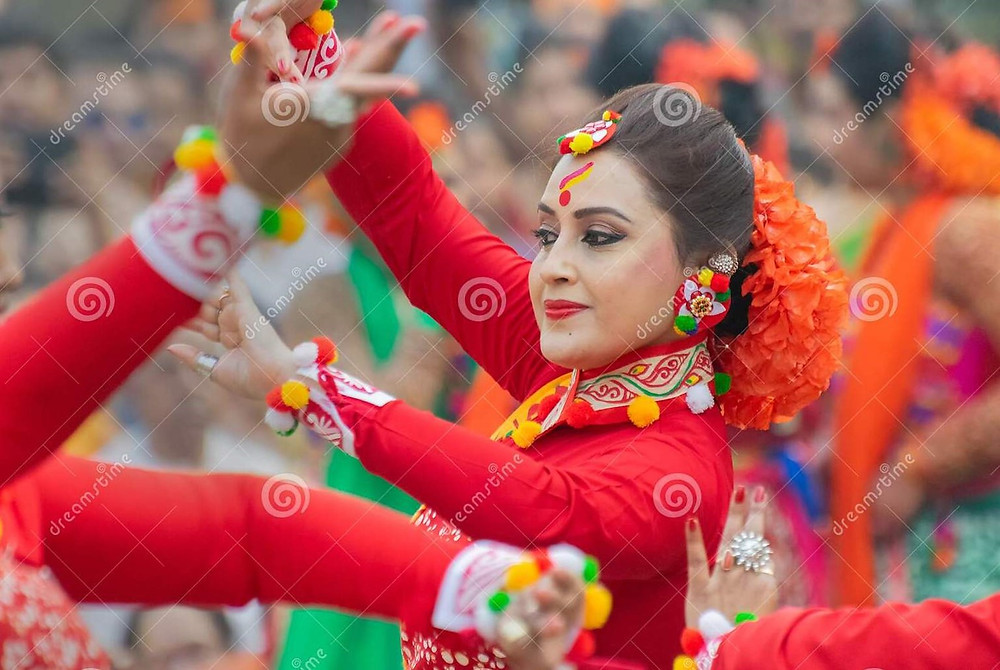 """This is a close-up photo of an Indian woman dancing during """"Basant Utsav."""""""