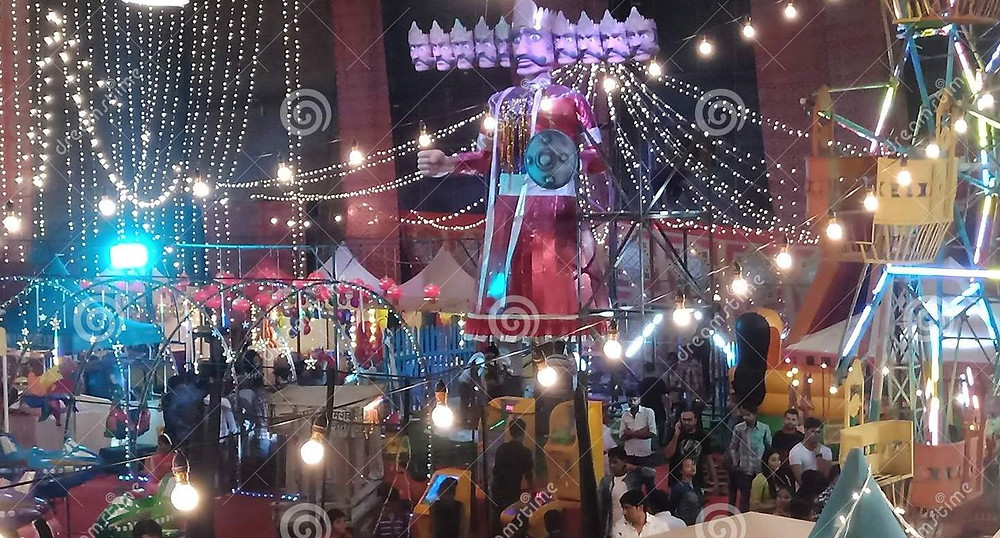 """This is a picture of the Indian Festival """"Dussehra."""" There are strings of lights, a Ferris wheel, several outdoor tents, and people walking around."""