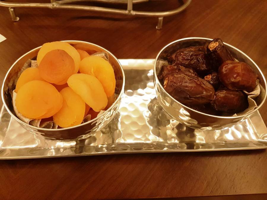 This is a picture of two small dishes. One has dried apricots, and the other has dried dates.