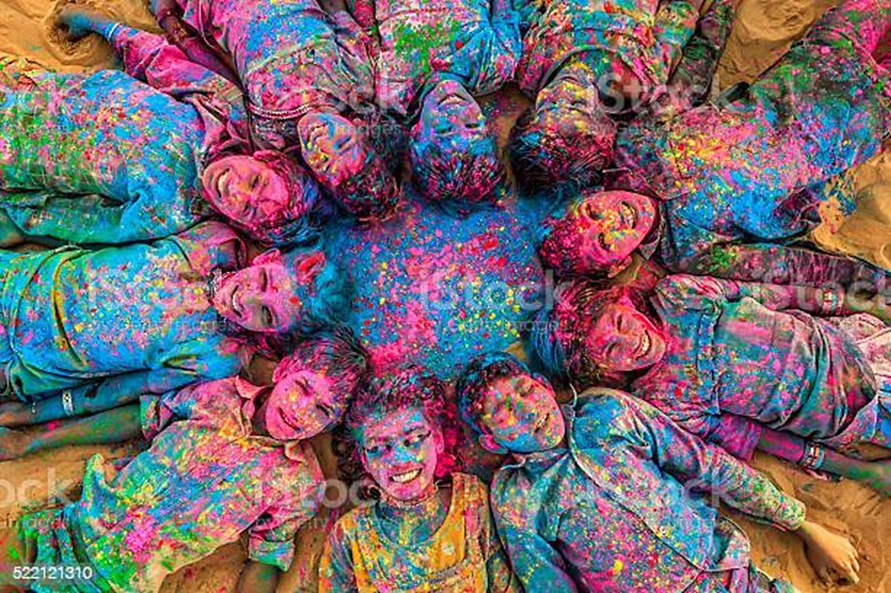 This is a picture of Indian children laying down in a circle. All of them are covered in Holi colors.