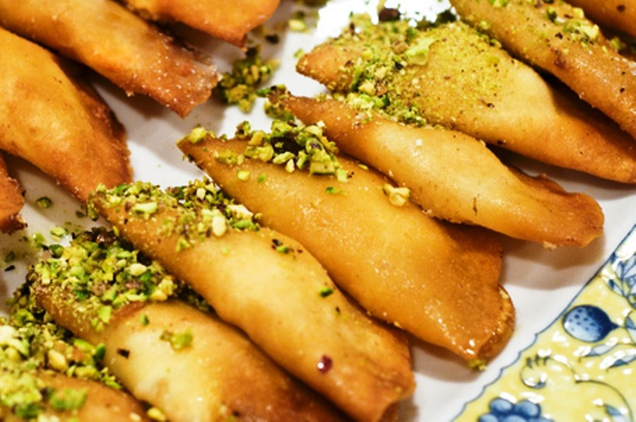 This is a picture of a tray of Qatayef with crushed pistachios sprinkled on top.