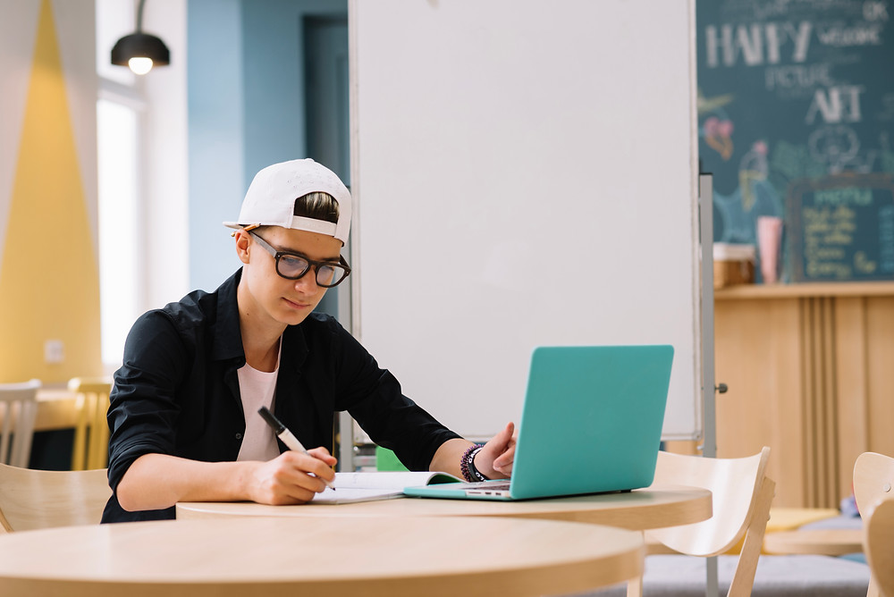 This is a picture of a male student sitting at a table in front of an open laptop. He's writing something in a notebook.