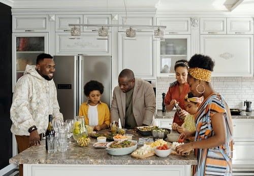 This is a picture of six Black individuals who are hanging out in a kitchen near an island. The island has a variety of appetizers. There are two men and a boy on one side of the island and two women and a girl on the other side.
