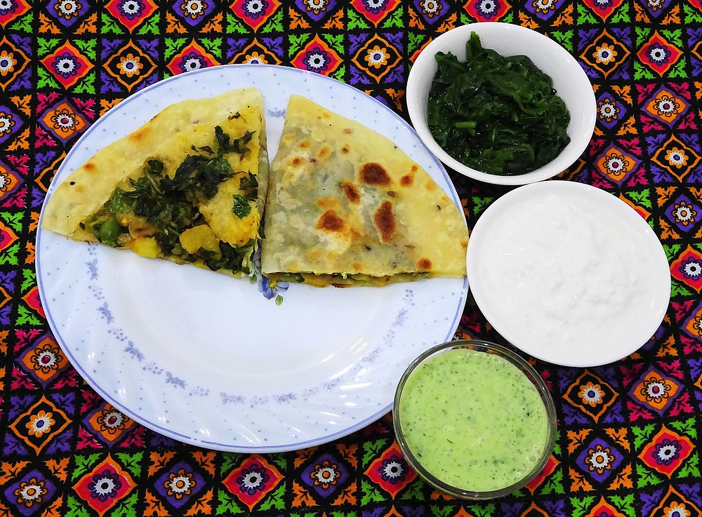 This is a picture of two slices of Bolani on a plate. Near the plate are three small bowls. One has cooked greens, one has a white dip, and one has a green dip.