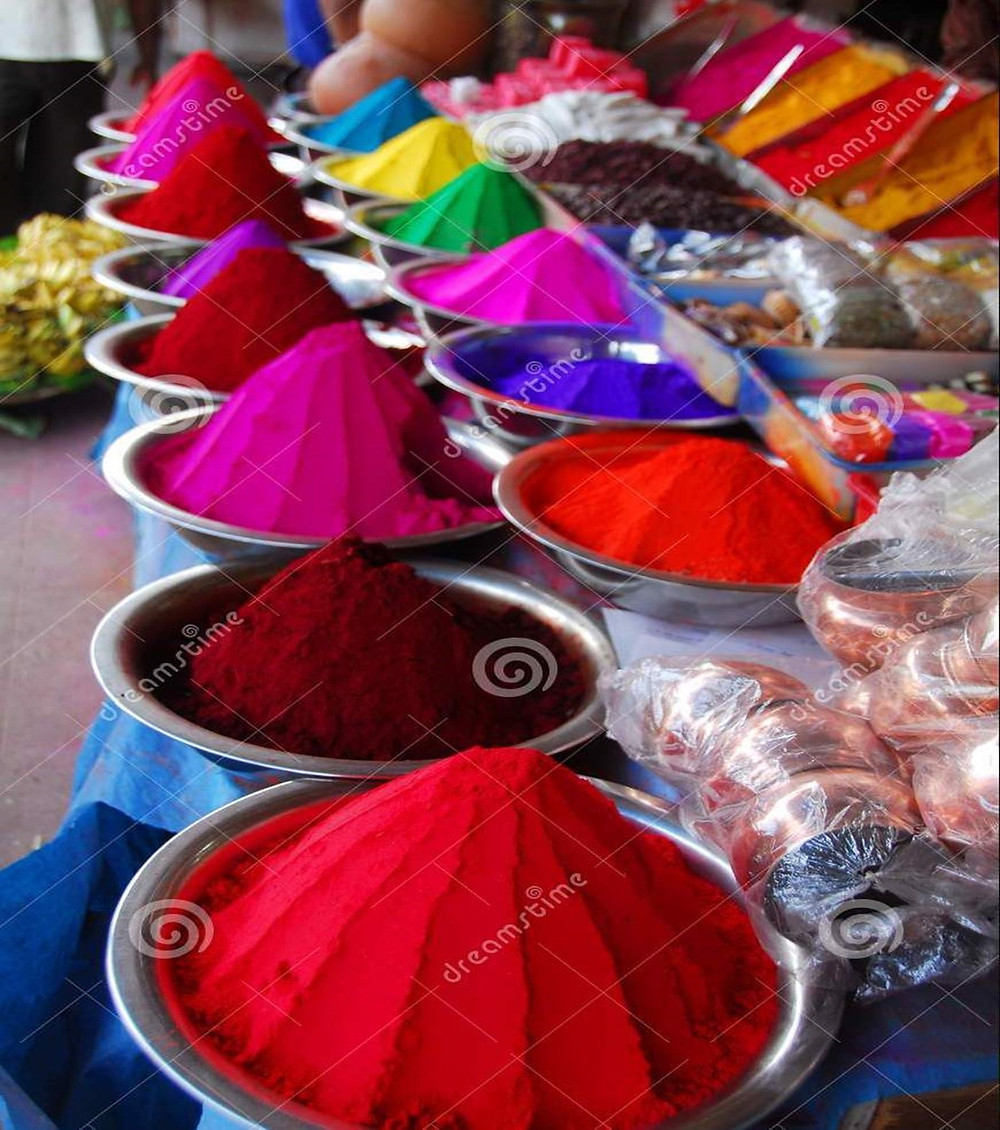 An assortment of dry Holi colors in metal tins on a table.