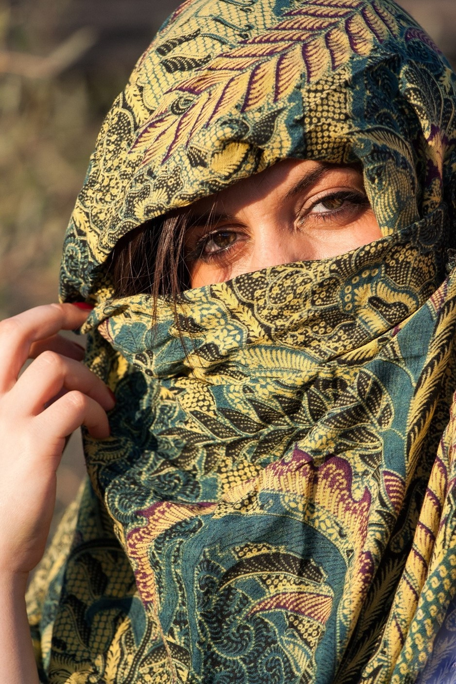 This is a picture of a woman wearing a green scarf with a leaf pattern around her head, with only her eyes and the bridge of her nose visible. She's using the middle finger on her right hand to draw back the scarf, revealing a small amount of brown hair.