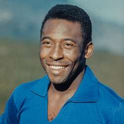 This is a picture of Pelé, a smiling Black man. He has short, black hair, and he's wearing a blue shirt. He's only visible from his head to his shoulders.