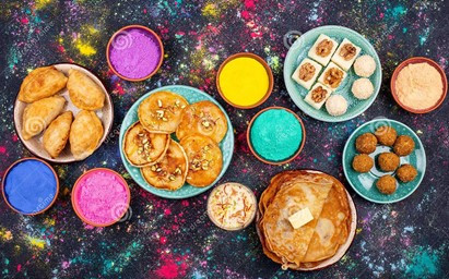 This is a picture of popular Holi snacks on different plates. There are aso five small cups that contain Holi colors.