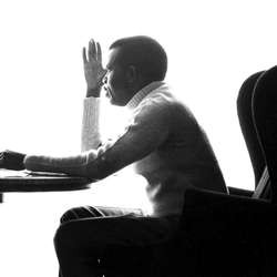 This is photograph of Chinua Achebe, a Black man. The picture captures his profile as he sits at a desk. He is wearing a light colored turtleneck and dark-colored pants.