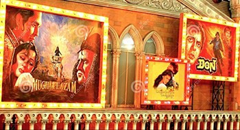 This is a picture of a red wall with three Bollywood movie posters on it.