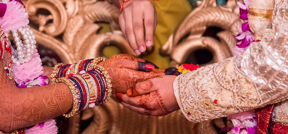 This is a picture of a man and a woman who are both holding hands. The woman's hands are covered in brown Henna tattoos, and she's wearing several bangles on both of her wrists. The man is also wearing some Henna tattoos, but only over his knuckles. Both are wearing ornate clothes, but no one's face is pictured. Above the hands is another hand wearing pink nail polish. The fingers are pinched together, as if the person is sprinkling something over the hands.