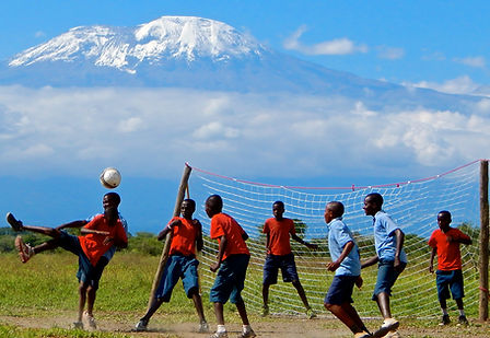 Mt. Kilimanjaro behind Maasai students playing soccer