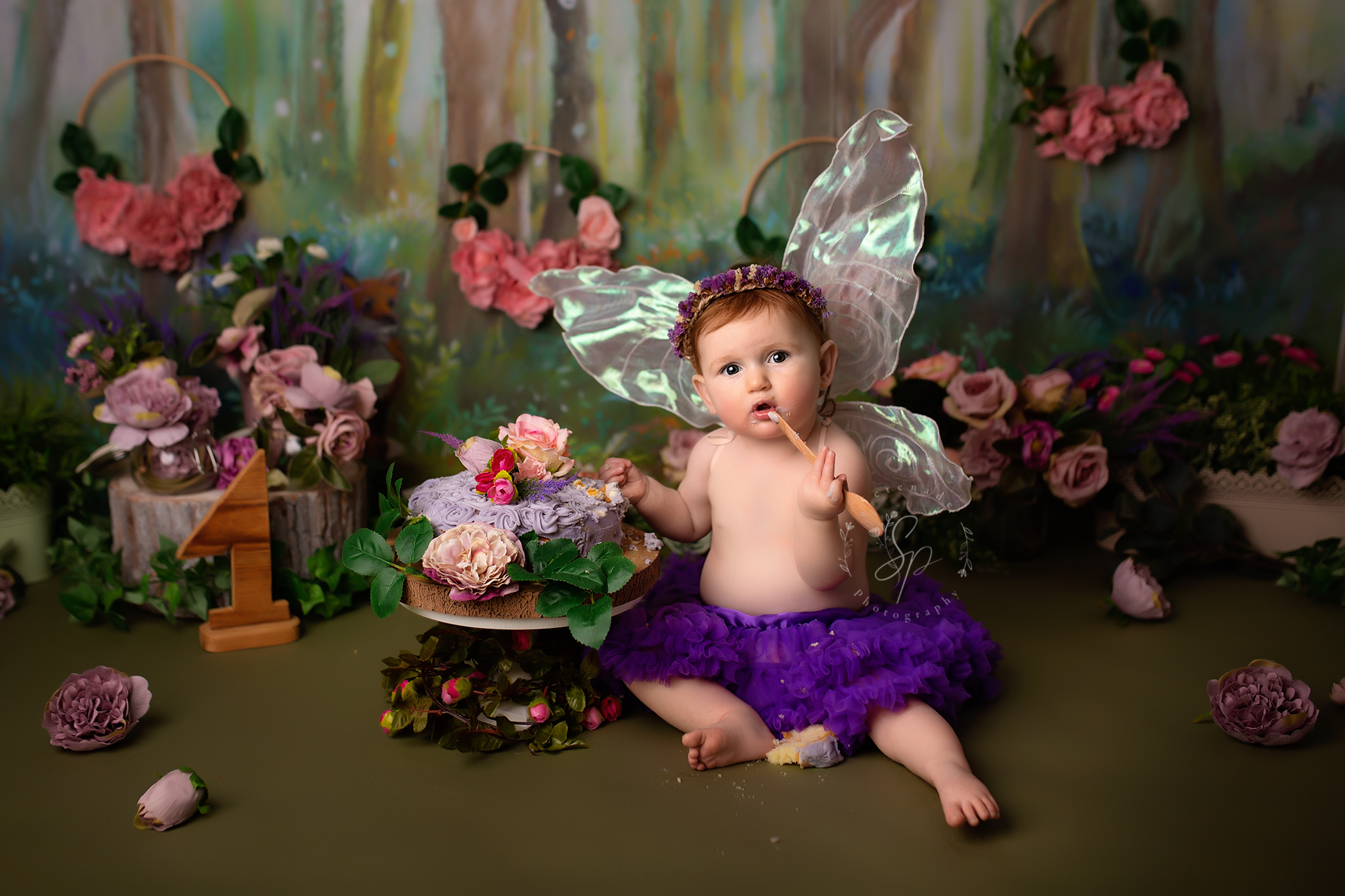 fairy themed first birthday photoshoot with girl wearing wings