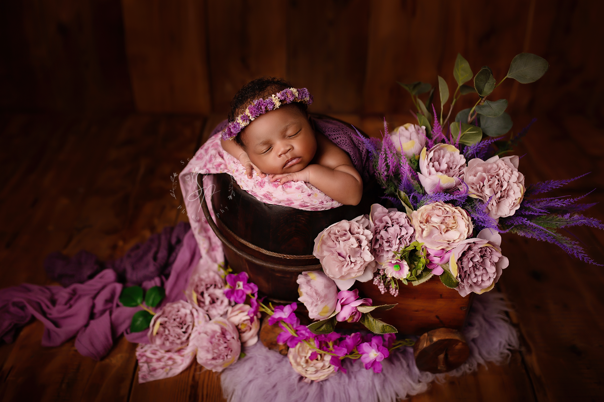 Newborn baby gril in the purple flower setup