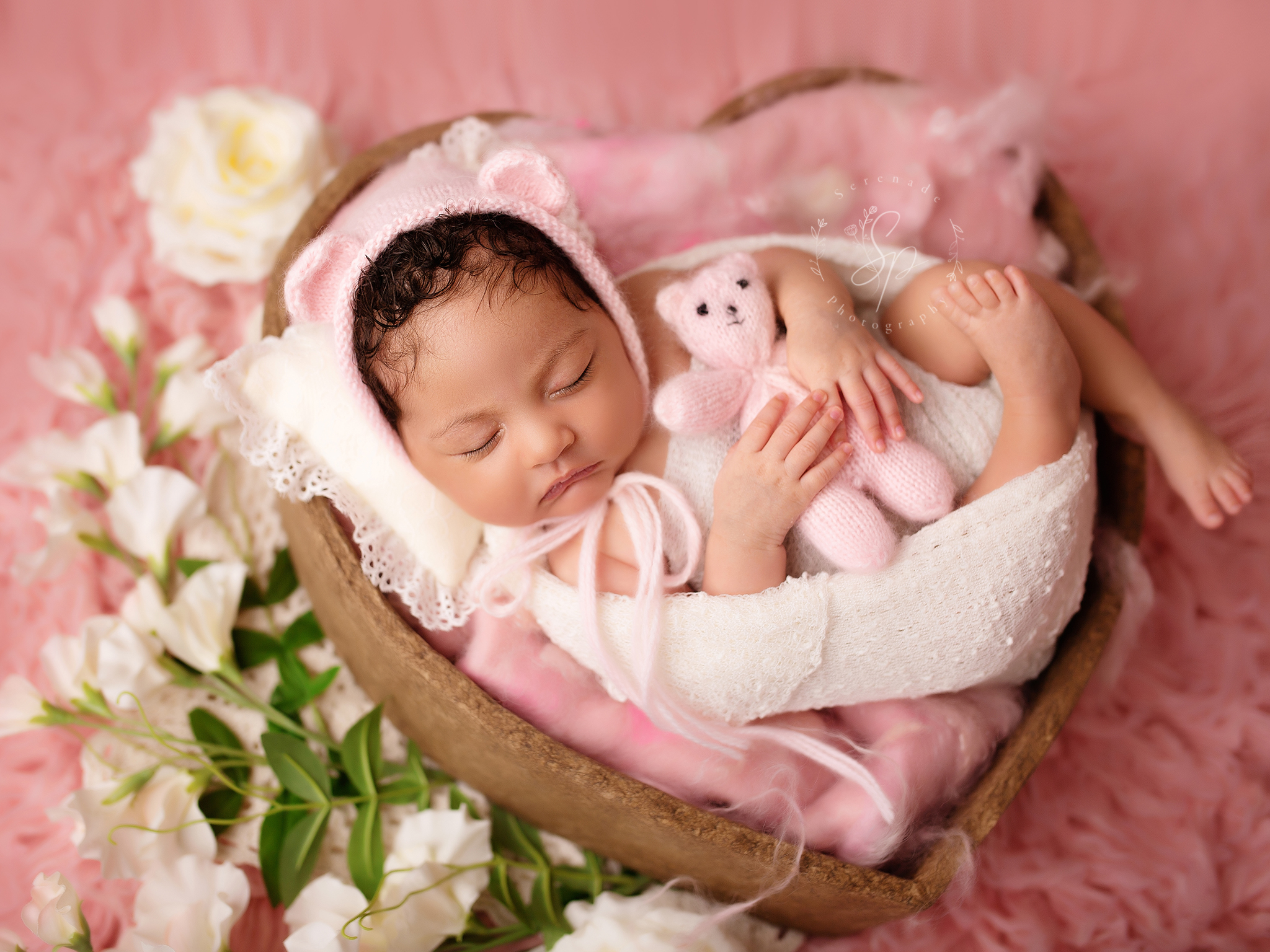 portrait of baby in pink teddy hat with toy