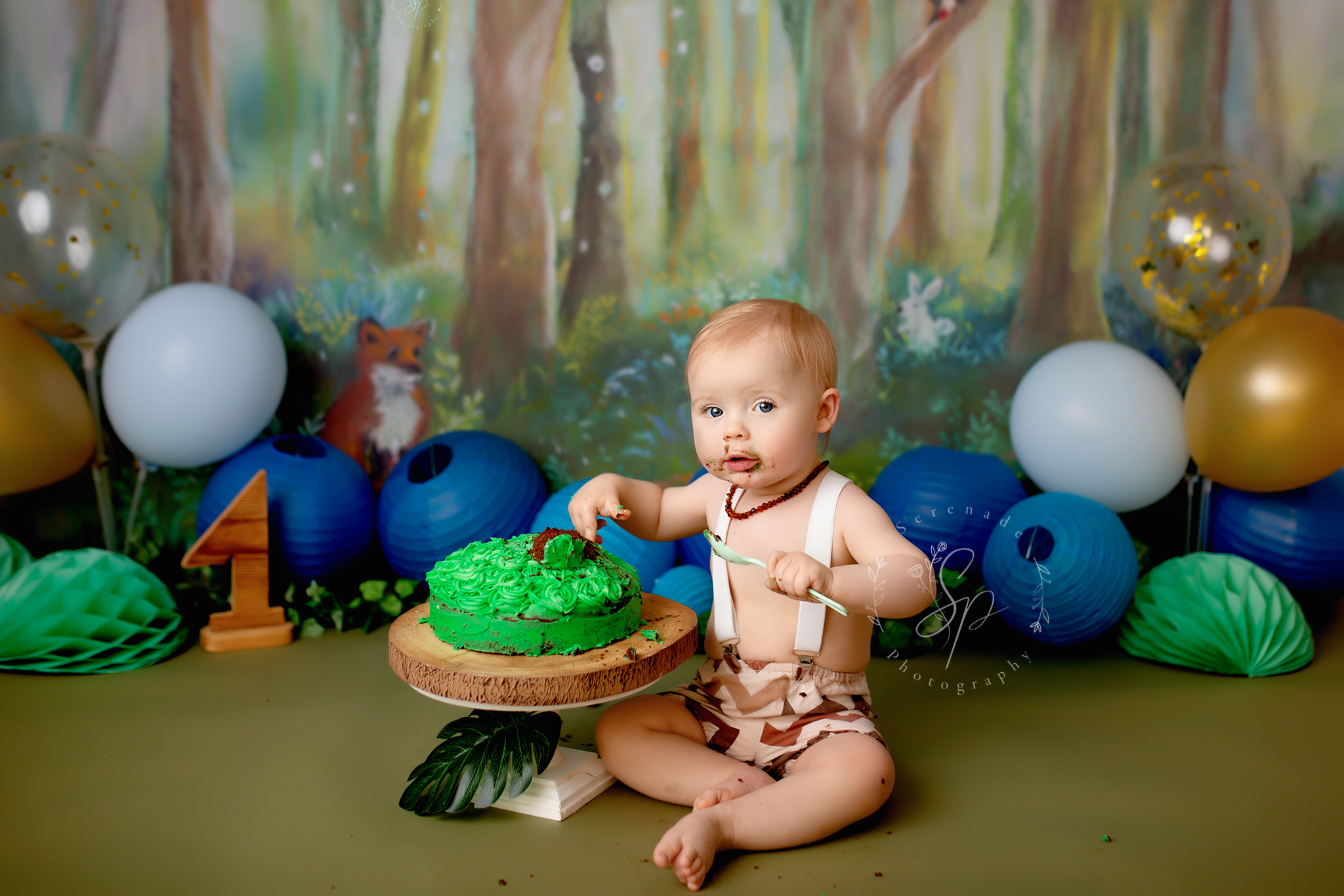 forest themed first bithday photoshoot with blues and green setup