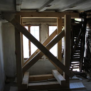 On the upper level, we build a bracing structure which transfers all the loads from the roof toward the ground-level support, thus relieving the damaged parts of the masonry and the wood structure from their load-bearing function.  На горния етаж издигнахме укрепителна конструкция, която да пренесе цялата тежест от покривния гредоред  към приземното укрепване, замествайки по този начин увредената част от зида и гредореда.